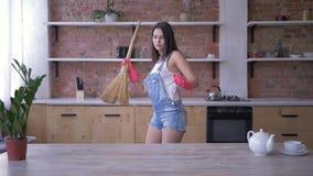 Рутинные работы по дому, жизнерадостная девушка домохозяйки околпачивая вокруг и танцуя в broomstick во время чистки дома видеоматериал