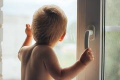 Ручка владением мальчика окна стоковое изображение rf