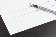 Ручка и белый лист на коричневой таблице стоковое фото rf