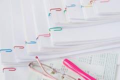 Ручка и зрелища положенные на банк книги Стоковая Фотография
