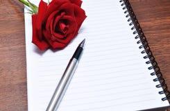 Ручка и красная роза на пустом блокноте Стоковые Фото