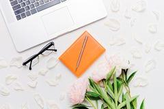 Ручка и пионы тетради стекел компьтер-книжки рабочего места Стоковые Фото