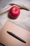 Ручка и тетрадь Яблока на белой cream ткани цвета Стоковые Изображения RF