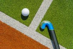 Ручка и шарик хоккея на траве на коричневой и зеленой траве стоковое изображение rf