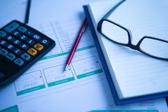 Ручка, калькулятор и стекла дела на финансовой диаграмме Стоковые Изображения RF