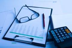 Ручка, калькулятор и стекла дела на финансовой диаграмме Стоковое Изображение RF