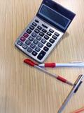 Ручка, карандаш и калькулятор на деревянной поверхности Стоковое Изображение