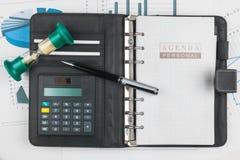 Ручка, калькулятор на тетради и часы стоковая фотография