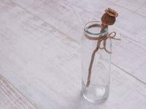 Ручка мака в стеклянной бутылке на белой таблице Стоковое Фото