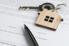 Ручка на печатном документе контракта согласования знака с ключом с древесиной Стоковая Фотография