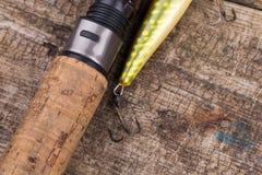 Ручка рыболовной удочки с прикормом на деревянном Стоковая Фотография