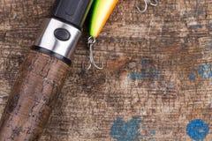Ручка рыболовной удочки с прикормом на деревянном Стоковая Фотография RF