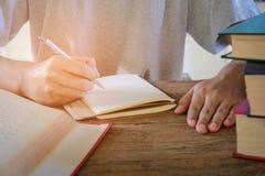 Ручка сочинительства человека в книге Стоковое фото RF