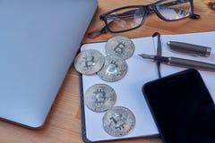 Ручка стекел, тетради и сочинительства мобильного телефона ноутбука Bitcoin серебряных монет рабочей зоны офиса портативная Конце стоковые изображения rf