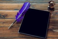 Ручка таблетки и пера на деревянной предпосылке Стоковое Фото