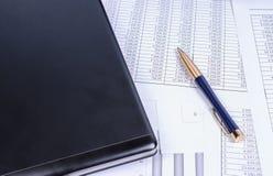 Ручка, тетрадь и бумаги на таблице владение домашнего ключа принципиальной схемы дела золотистое достигая небо к Стоковое Изображение RF