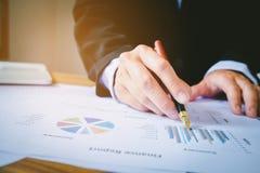 Ручка удерживания бизнесмена указывая на диаграмму отчетного доклада Стоковая Фотография