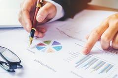 Ручка удерживания бизнесмена указывая на диаграмму отчетного доклада Стоковые Фото