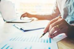 Ручка удерживания бизнесмена указывая на диаграмму отчетного доклада Стоковое Фото