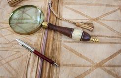Ручка лупы и шариковой авторучки лежа на кожаной папке Стоковое Изображение RF