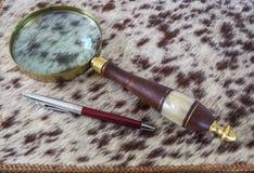 Ручка лупы и шариковой авторучки лежа на кожаной папке Стоковое Фото