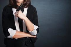 Ручка удерживания бизнес-леди Азии и думать на пустой стене для стоковое фото
