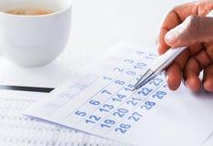 Ручка удерживания руки человека на календаре Стоковые Изображения RF
