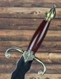 Ручка шпаги на деревянной предпосылке стоковые изображения rf