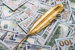 Ручка quill золота на предпосылке денег доллара Стоковые Изображения