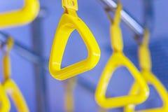 Ручки желтого цвета на рельсах потолка для стоящего пассажира Ручка o Стоковое Изображение