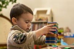 Ручки младенца делают башню из пестротканых игрушек Стоковое Фото