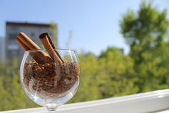 Ручки циннамона в бокале вина с раздробленным кофе, дневном свете Стоковые Фотографии RF