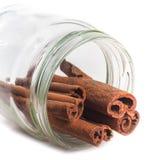 Ручки циннамона в опарнике на белой предпосылке стоковая фотография rf