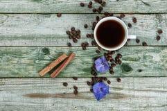 Ручки циннамона, зерна кофе и кофе чашки на старой деревенской зеленой предпосылке Взгляд сверху Стоковая Фотография RF