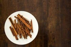 Ручки циннамона и белая плита на деревянной столешнице Стоковое Изображение RF