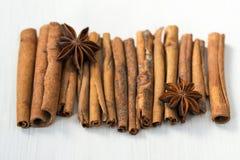 Ручки циннамона и звезды анисовки на белой деревянной предпосылке Стоковые Изображения
