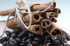 Ручки циннамона с веревочкой на черных кофейных зернах стоковые фото