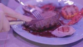 Ручная резка девушки большая соединяет мяса и наслаждается ее едой в современном ресторане Сладкая мозоль, перец chili и видеоматериал