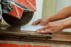 Ручное вырезывание керамических плиток на специальной машине для резать плитки Стоковое фото RF
