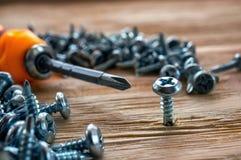 Ручные винты и шпонки отвертки на деревянной предпосылке стоковая фотография rf
