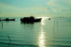 Рыбацкая лодка захода солнца силуэта на itподготавливает к удить стоковое изображение rf