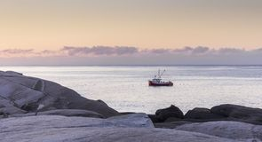 Рыбацкая лодка на зоре на бухте ` s Пегги в Новой Шотландии, Канаде стоковые фото