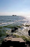 Рыбацкая лодка в море около горизонта, прибой ударяет утесы Стоковая Фотография