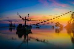 Рыбацкая лодка и дерево силуэтов на времени захода солнца Стоковая Фотография RF