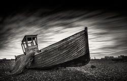 Рыбацкая лодка, который сели на мель на pebbled пляже Dungeness, лачуги England Стоковое Изображение
