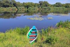 Рыбацкая лодка на живописном банке реки Стоковая Фотография