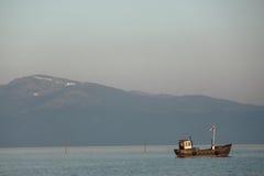 Рыбацкая лодка на предпосылке большой горы стоковые изображения rf