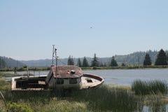 Рыбацкая лодка покинутая на береге в Reedsport, Орегоне Стоковое Изображение RF