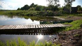 Рыбацкая лодка причалила на озере в утре в лете сток-видео