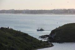 Рыбацкая лодка среди утесов в море Стоковое фото RF